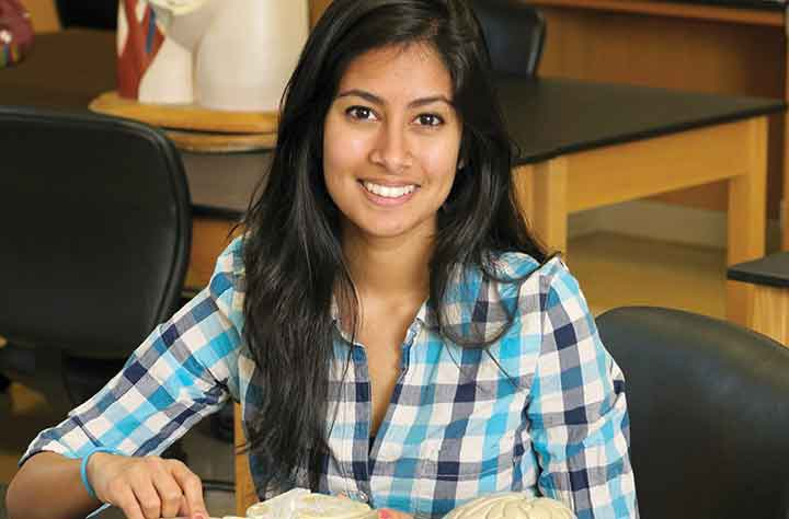 alumnae ADITI DEY '13 sits at desk with book open