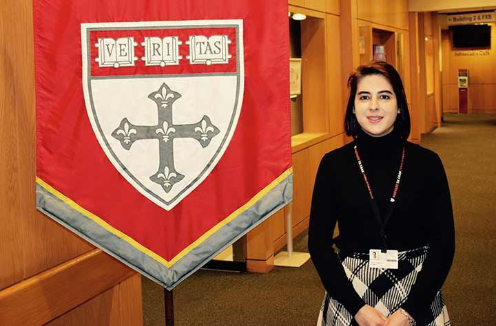 Maria stands in front of Harvard flag.