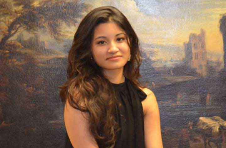 Alumnae AAHANA BAJRACHARYA '16 poses for the camera in front of a landscape painting