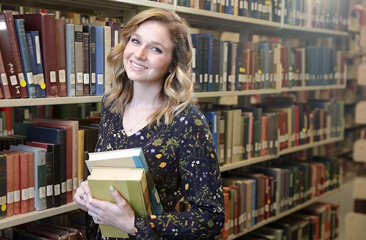 Amber Davis holding books in Willet Library.