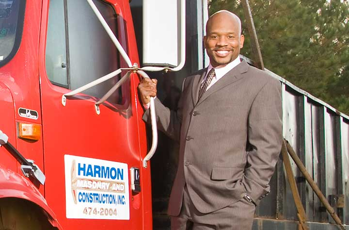 Adrian Harmon stand with his company truck.