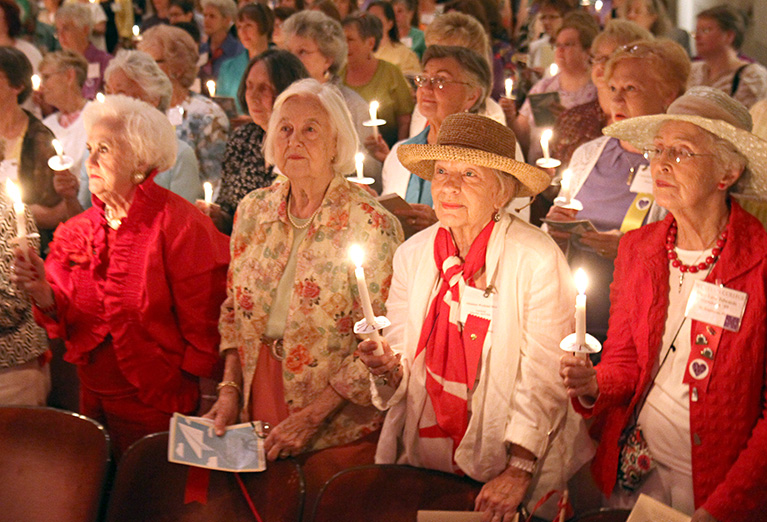 Alumnnae hold candles during ceremony in Porter