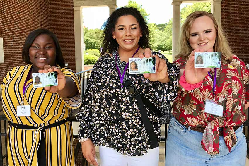 Three students hold up their new student id badges
