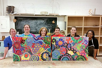 Six MEd students stand behind two colorful abstract paintings in the art building.