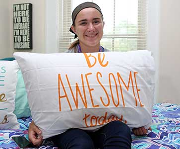 Wesleyan College student in her dorm is holding a pillow with