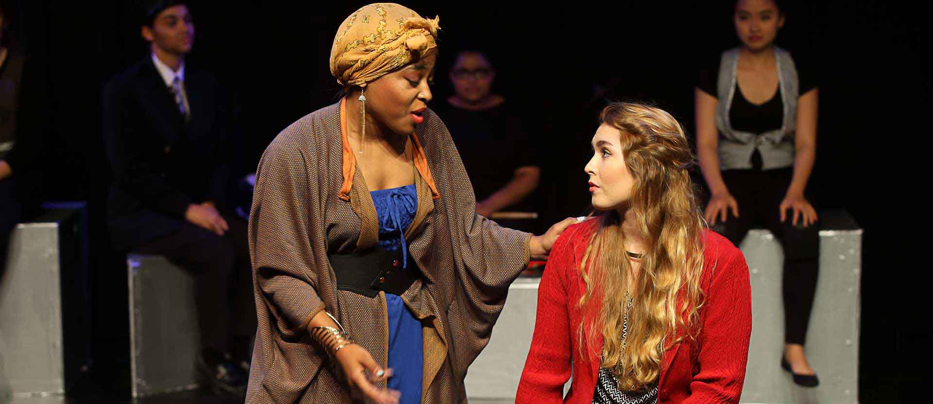 Theatre production of students acting. One women leans sympathetic arm on woman sitting down and upset.