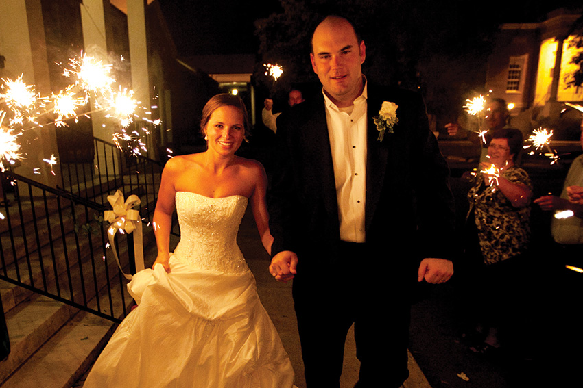 Bride and Groom walk to car at night with sparklers in the background