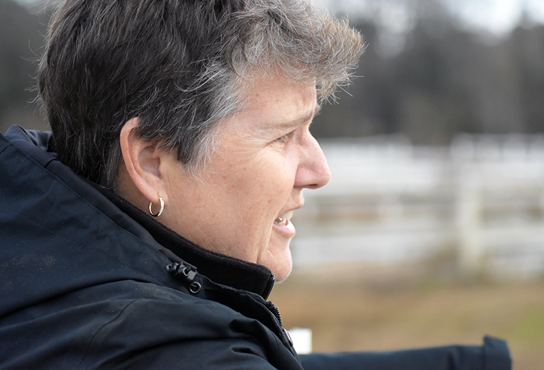 Head Equestrian Coach Catherine Baker looks out on the horses.